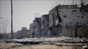 A man walks through Tripoli street in the besieged city of Misrata, 26 April 2011