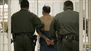 Inmate in a California prison being escorted by guards