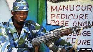 "A fighter from the ""Invisible Commandos"" militia stands guard outside a beauty salon near a villa headquarters in the Abobo neighbourhood of Ivory Coast's main city Abidjan 19 April 2011"