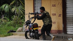 An alleged member of the Farc guerrillas aims a rifle in Cauca province on 8 April 2011