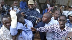 Ugandan opposition leader and former presidential candidate Dr Kizza Besigye, second left with plaster on his right hand is arrested by security personnel in Kampala city centre, Thursday 28 April 2011