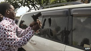 A Ugandan plainclothes policeman smashes the window of opposition leader Kizza Besigye in Kampala, on 28 April 2011