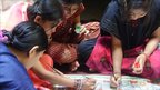 Women working on Madhubani paintings in the Indian state of Bihar