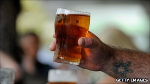 A patron lifts a glass of beer in Sydney.