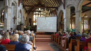 A crowd watch the wedding at St Dunstan's Church in Mayfield