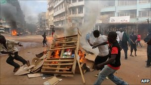 Rioters fuel a burning barricade during riots in Kampala, Uganda, on 29 April 2011