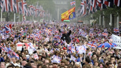 Crowds throng down the Mall to Buckingham Palace where the royal couple are expected to appear for a kiss on the balcony