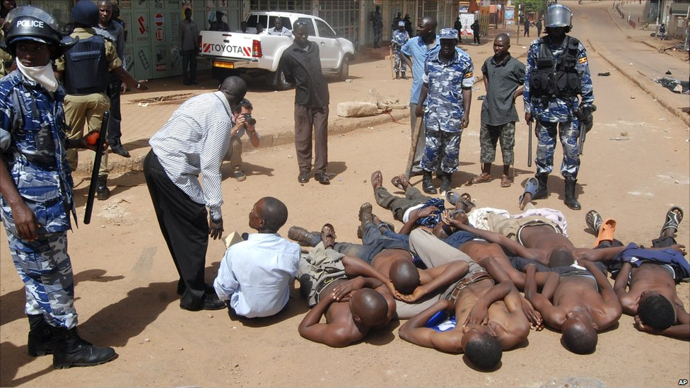 Ugandan protesters are made to lie down on the road after their arrest by Ugandan police in Kampala, Friday 29 April 2011