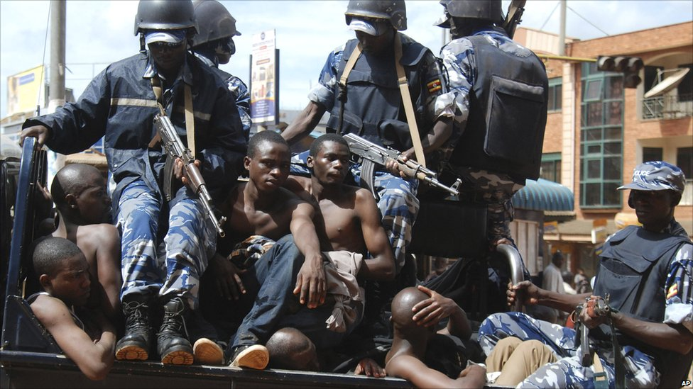 Rioters sit on the back of a police truck after their arrest in Kampala, Friday, April 29, 2011 after riots broke out
