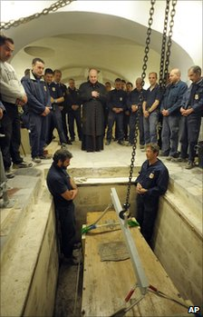 Workers pause for prayers before removing Pope John Paul II's coffin from its crypt in St Peter's Basilica, the Vatican, 29 April