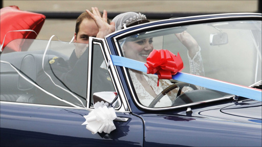 The couple leave Buckingham Palace in an open top car, apparently his father's Aston Martin