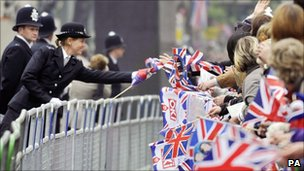 A police officer passes a flag to a member of the public