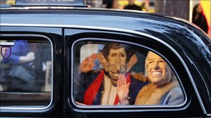 A man and woman dressed as Prince Charles and Queen Elizabeth II wave from inside an English cab in Sydney