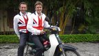 Two men in Union Jack waistcoats on a motor bike.