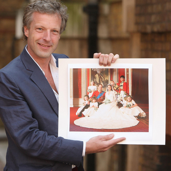 Hugo Burnand, the official royal wedding photographer, holds up one of his pictures of the newly married couple.