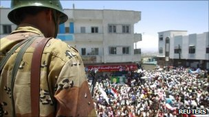 A Yemeni soldier watches anti-government protesters in the city of Taiz, 30 April