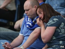 A Stockport fan wipes away a tear during one of their final matches