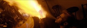 A man with a full throat of absinthe spits fire during a party at a bar in Prague, Czech Republic