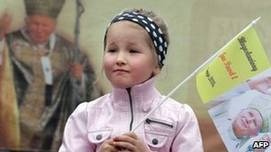 A girl holding flag with an image of John Paul II in Wadowice, southern Poland, on 1 May 2011