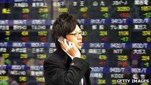 Man walks past Tokyo stock market board.
