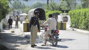 A Pakistani police officer talks to a motor cyclist at a security check post in Abbottabad, Pakistani on Monday, May 2, 2011.