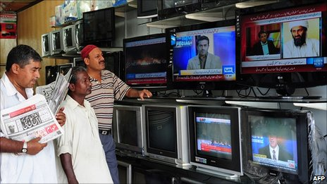 Pakistani viewers watch television news broadcasts at an electrical store in Karachi on 2 May 2011, which are showing details of the death of Al-Qaeda leader Osama bin Laden