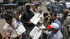 Pakistanis in the southern city of Karachi buy newspapers reporting the killing of al-Qaeda leader Osama Bin Laden