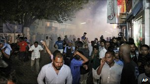 People cover their noses and run for cover as riot police use tear gas in Male