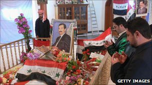 Men pray at Saddam Hussein's resting place