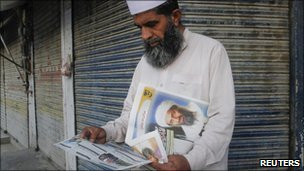 A man reads newspapers with Osama Bin Laden on the cover in Abbottabad on 3 May, 2011