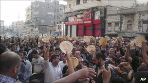 Syrian men carry bread loaves during a protest against President Assad in Baniyas on 3 May (citizen journalism image)