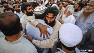 Supporters of the banned Islamic organization Jamaat-ud-Dawa embrace each other after taking part in a funeral prayer for al Qaeda leader Osama bin Laden in Karachi May 3, 2011.