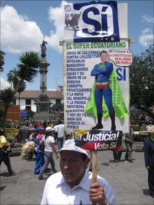 Luis Simba carries a placard with an image of Rafael Correa as a superhero