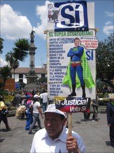 Luis Simba carries a placard with an image of Rafael Correa as a superhero
