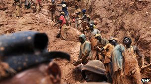 Miners standing on a muddy cliff at a gold mine in Chudja, near Bunia, north eastern Congo