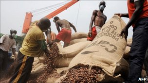 Ivorian workers empty bags of cocoa beans in a container at the Port of Abidjan where 80% of Ivory Coast's exports transit