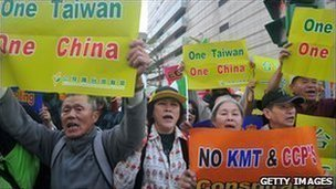 Anti-China demonstrators hold placards during a rally outside a hotel in Taipei.