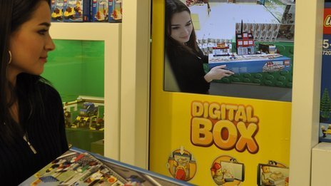 A shopper examines an augmented reality 3D Lego model before deciding whether to buy