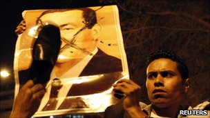Anti-Mubarak protesters deface a picture of the former president. Photo: April 2011