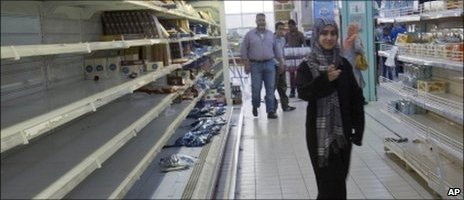 Libyans walk in between near empty shelves at a supermarket in Tripoli, Libya, Tuesday 3 May 2011