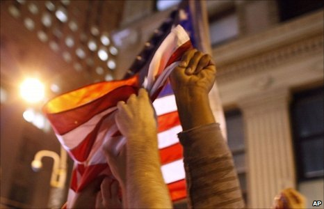 Hands reach up to grasp an American flag as a large, jubilant crowd reacts to the news of Osama Bin Laden's death at the corner of Church and Vesey Streets