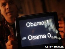 A man holds up a scoreboard on his ipad displaying Obama - one, Osama - nil