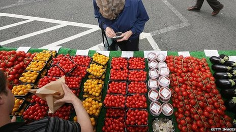 A woman buys tomatoes at a farmers' market in Wimbledon