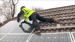 Solar panel installer drilling panels to a roof