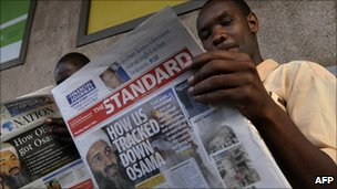 Kenyan men read local dailies with the headline on 3 May 2011 How Obama got Osama in Nairobi