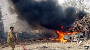 A Pakistani firefighter shouting in front of burning vehicle used by a suicide bomber