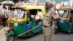 An Indian police officer keeps traffic moving in Delhi