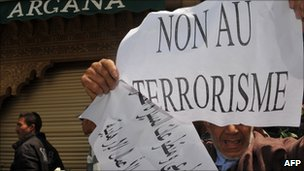 A man holds a sign in front of the Argana Cafe in Marrakesh during a demonstration (7 May 2011)