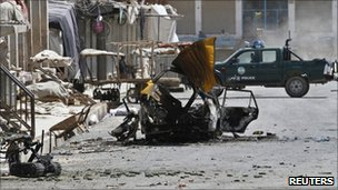 Debris from a car bomb is seen on a road in Kandahar city on 8 May 2011
