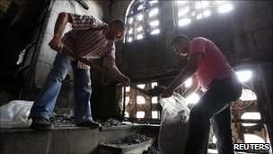 Christians clean up a church damaged by fire in Cairo, Egypt (8 May 2011)